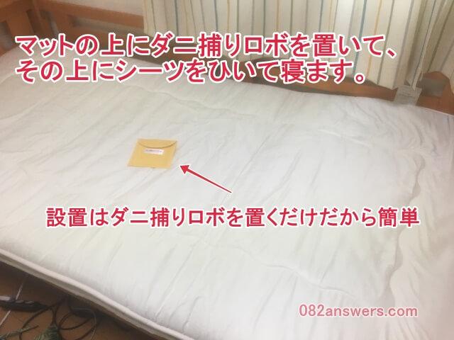 ベッドにダニ捕りロボを設置した画像です。マットの上にダニ捕りロボを置くだけで設置完了です。